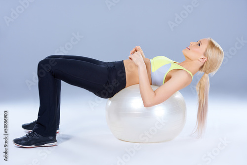 Spotty woman lying on fitness ball