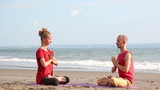 Couple sitting in pose lotus and practicing yoga on beach