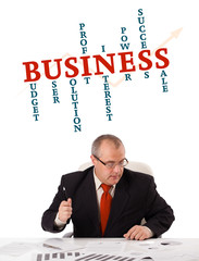 businessman sitting at desk with word cloud