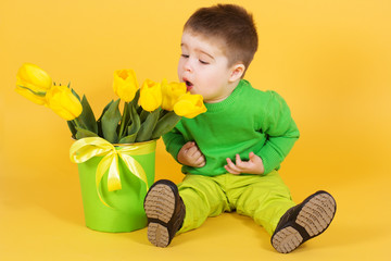 Little baby boy with bouquet of yellow tulips