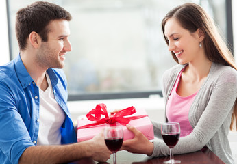 Man giving woman gift at cafe