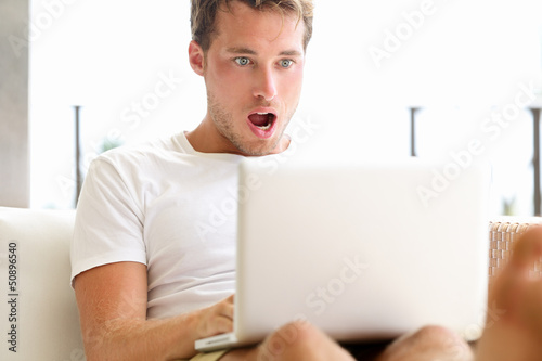 Shocked surprised man looking at laptop computer