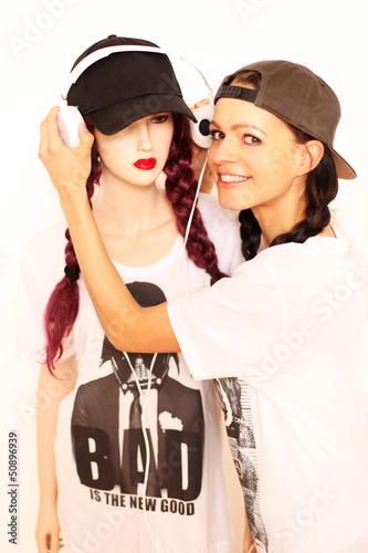 Frau mit Kopfhörern und Schaufensterpuppe