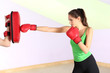 Young beautiful woman with boxing gloves at workout, at gym