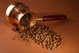Coffee pot with coffee beans on brown background