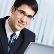 Smiling businessman working with laptop at office