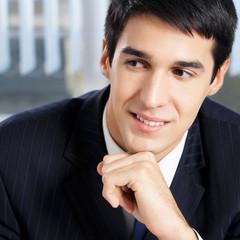 Portrait of thinkihg businessman at office
