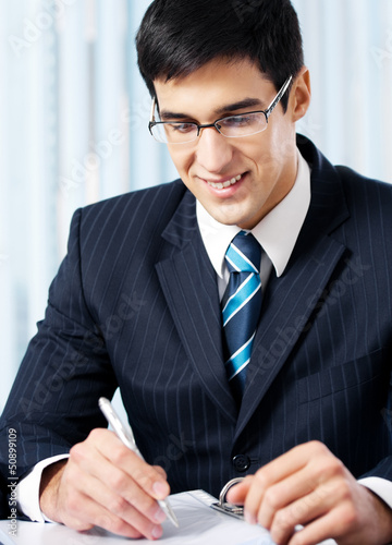 Portrait of writing smiling businessman working