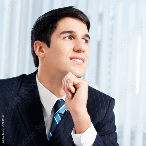 Portrait of thinkihg businessman at office