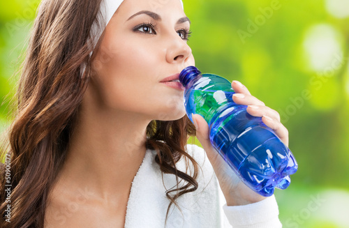 Woman drinking water, outdoors