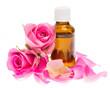 Rosenöl mit Rosenblüten auf weißem Hintergrund