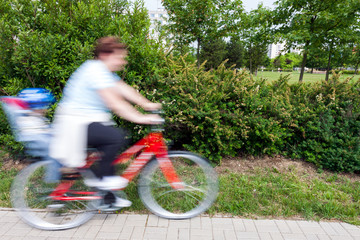 woman with child on bicycle - panning image