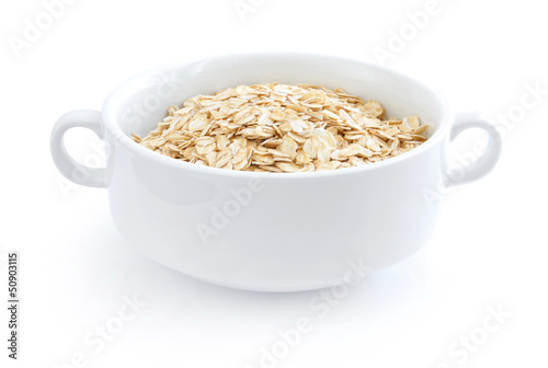 Oat flakes in white bowl on white background