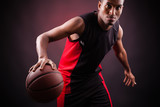 Fototapeta Portrait of a young male basketball player against black backgr