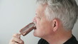 profile of man eating ice cream bar