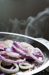 red onion cooking in frying pan