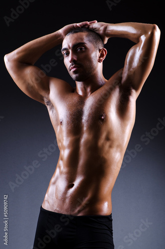 Muscular man in dark studio