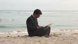 Handsome businessman sitting at beach and typing on laptop