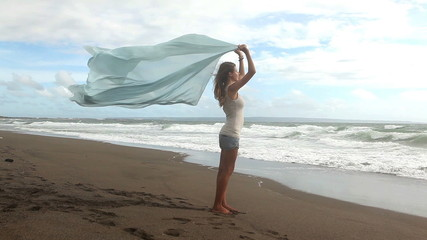 Pretty young woman holding textile and enjoying ocean view