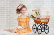 Girl in orange dress with vintage pram