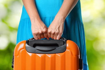 Woman in blue dress holds orange suitcase in hands on natural ba