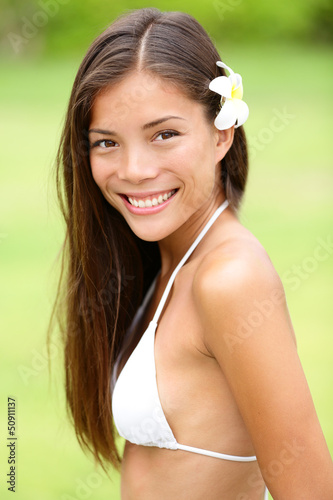 Bikini girl wearing Hawaiian flower smiling fresh
