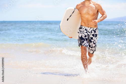 Beach fun surfer man running with bodyboard