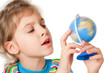 A little girl looks at a small globe