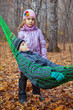 A boy with his sister relaxing in hammock in autumn forest