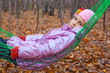 Thoughtful girl swinging in hammock in autumn forest
