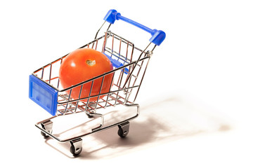 A big red tomato in a small shopping cart isolated