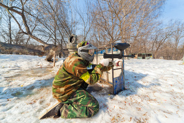 player in a paintball aims for shelter in game on sunny day