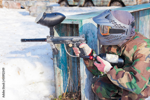 player in paintball aims for shelter in game on sunny day
