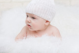 Side portrait of a concentrated baby in a white hat