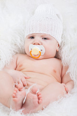 Portrait of a baby with a pacifier in white hat