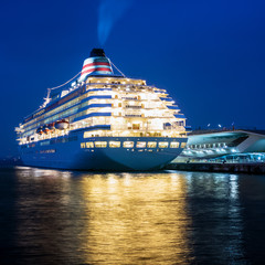 Huge luxury cruise ship putting off from pier at night.