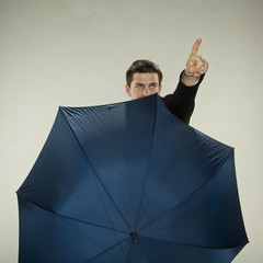 businessman is hiding behind umbrella