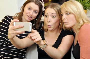Junge Frauen fotografieren sich per Smartphone