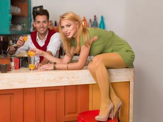 happy couple preparing and orange beverage