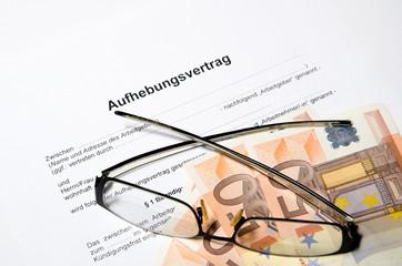 Aufhebungsvertrag mit Geld und Brille