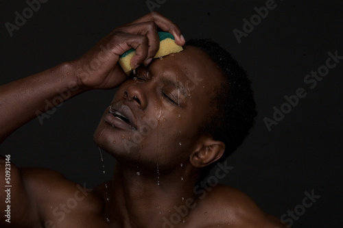 Portrait of a Sexy Man Washing Face with Water
