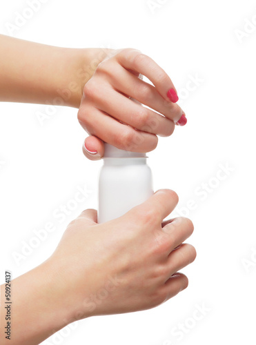 Beautiful female hands opening the bottle with a talcum powder