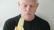 man peels and eats banana