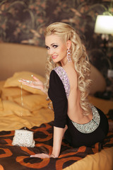 Fashion blonde woman in hotel. Hairstyle and make up