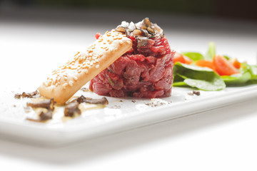 Elegant Seasoned beef tartare with black truffles. Gourmet Delic