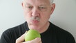 man eats green apple front view