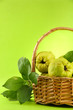 sweet quinces with leaves in basket, on green background