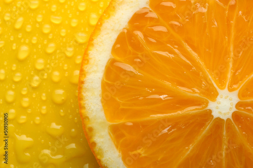 Slice of orange with drop on yellow background