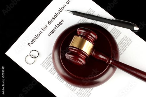 Divorce decree and wooden gavel on black background