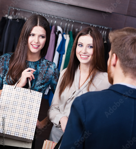 Two young girls speak to shop consultant